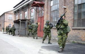 På rad tar sig soldaterna fram för att inta ett hus.