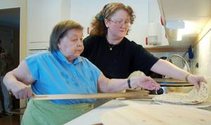 Elvira Åhrén gräddar ytterligare ett tunnbröd, och får lite hjälp av Birgitta Eliasson.