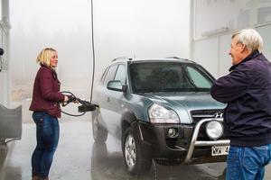 Malin Wallin, Ängebo, Bjuråker kommenterar tvättanläggningen till  ägaren Leif Johansson medan hon tvättar bilen.