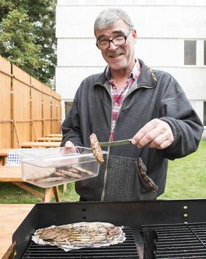 Vaktmästare på Nivrenaskolan Peter Günter grillade och serverade hamburgare åt de nyanlända.