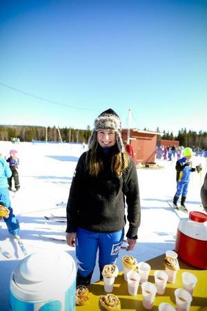 Sofie Björklund, skidgymnasieelev, serverar saft och bulle till alla deltagare.