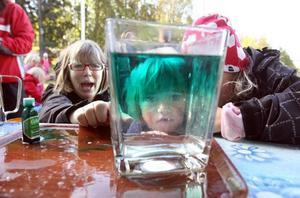"""Vad händer om man häller varmt vatten i kallt? Genom att blanda karamellfärg i det varma vattnet visar Lotta Wåhlin barnen hur det blir. """"Titta, det gröna hamnar uppe. Det som var varmt"""", säger Elsa Palmberg imponerat."""