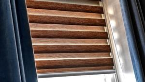 En randig hissgardin i två lager ger möjlighet att justera solljus och insyn.