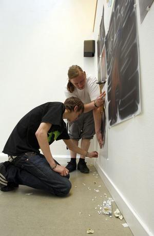 Mattias Gunnarsson-Embretsen och Nils Danhard från årskurs två har fullt sjå med att hänga sina air-brushmålningar.