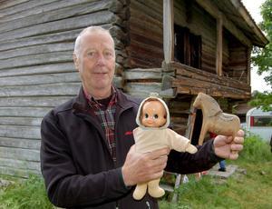 Per-Erik Larsson med en gammal trähäst och en docka med två ansikten.