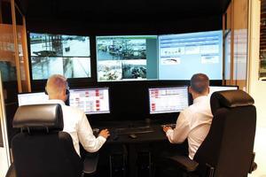 Styr containrar. Fredrik Rönnqvist och Håkan Törnqvist jobbar faktiskt på riktigt. De styr Gävle Containerterminal från mässgolvet i Göransson Arena.
