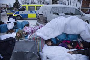 Tidigare denna månad lämnade flyktingar asylboendet Trängslet i norra Dalarna på grund av bråk och våldsamheter och reste till Migrationsverkets huvudkontor i Märsta. Barnen Nor, Saleh och Hajaj Fatema från Syrien värmde sig under täcken