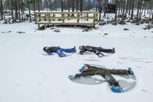 Aleksander Grishin och bakom honom Simon Johansson och Dominick Lindberg gjorde snöänglar nära den nya bryggan som tillåter rullstolsburna och andra funktionshindrade att fiska med spö i Stortjärn.