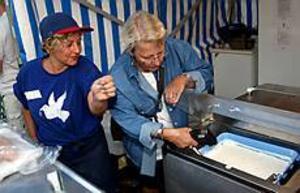 Foto: LASSEWIGERT Koll på kylan. Livsmedelsinspektör Ann-Katrin Lunt tar tempen på festivalmaten hos ståndet som säljer grekiska grillspett vid gudinnan. Zoula tittar lugnt på, hon vet att allt är bra.\n\n