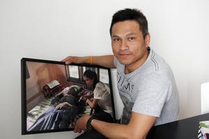 Surasuk Wanrach med en av bilderna i fotoboken, där hans syster sköter om den döende pappan.