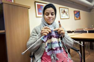 Zahra Tafwiz stickar en tröja.