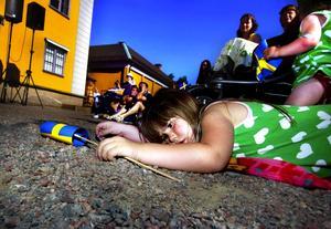 Trött av flaggviftande. Fyraåriga Alva Wikström tog en paus i nationaldagsfirandet vid Falu gruva.