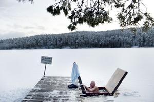 Harald Lindgren tar sig ur isvaken i Stångtjärn. Han har vinterbadat sedan stugan byggdes 1945 men på den tiden fick de hacka upp isen berättar han.