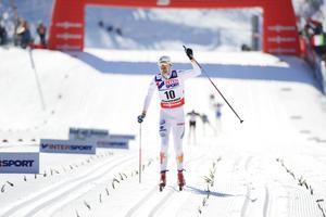 Johan Olsson lyfter handen när han glider in över mållinjen i Val di Fiemme efter vinsten i femmilen.