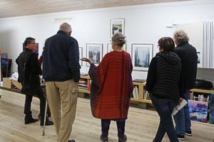 Gunilla Ellis berättar mer om några av av tavlorna på väggen. Hon hade fullt upp hela helgen