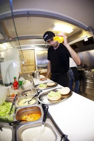 Idris Gönültas ser till att hamburgaren förses med en lagom dos av senap.