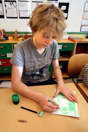 Rikard Cedergren tvingas vässa den gröna pennan om och om igen för att få till sin gröna teckning av en fotbollsplan.