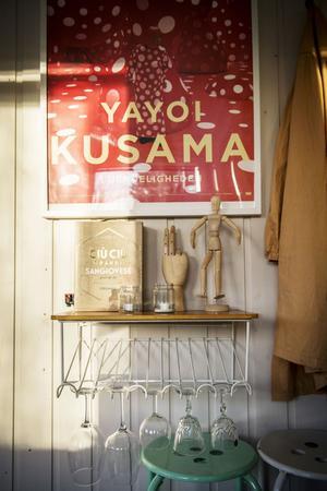 En gammal telefonbänk förvarar vinglasen i ateljén på ett fiffigt sätt.