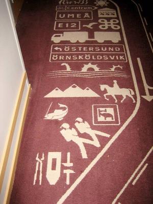 Den vackra mattan i korridoren visar en del av Jämtlands läns vapen, vandrare, fjäll, Storsjöodjuret.