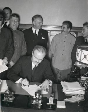23 augusti 1939. Molotov-Ribbentrop-pakten undertecknas i Moskva. Pakten innebar att östra Europa delade upp mellan Tyskland Och Sovjet. Vid bordet sitter den ryske utrikesministern Molotov, bakom honom syns den tyska utrikesministern Ribbentrop i samspråk med Stalin. Knappt två år senare var de båda länderna i krig med varandra.    Foto: Hoffman/PrB