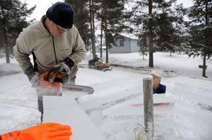 Torbjörn Persson kantsågar ett isblock.