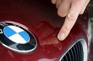 Lacken borta. Klarlacken har lossnat på flera mindre ytor på bilens motorhuv. I kanterna kan man se smala fält av lack som tappat kontakten med grundlacken.
