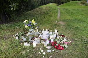 Många har lämnat ljus och blommor i utkanten på parken där mordet på kvinnan inträffade.