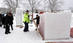 Hans Fors i den gula jackan har kört runt på åkrarna kring Wij och skopat upp snö till tävlingen. Snön har han sedan packat i en stor träform och i går var det dags att plocka fram snöblocken när snöskulpturtävlingen på Wij trädgårdar startade.
