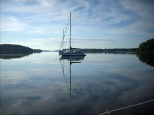 Morgon i Hästskoviken. Absolut vindstilla. Fortfarande sover man i grannbåtarna på svaj, men vi smyger iväg förbi dem, lugnt och i sakta mak så vi inte väcker någon i den tidiga morgonen.