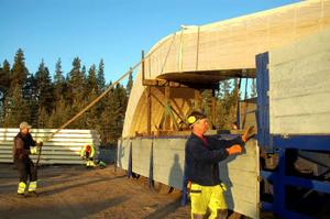 Jörgen Vesterinen och Urban Trygg hjälper killarna från Töreboda Limträ att lossa stommen till ridhuset.  Foto: Carin Selldén