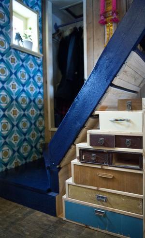 Till hallen har Sara valt en gammal vinyltapet som hon hittade på Larshans antikt och kuriosa i Falun. Under trappan syns Saras senaste projekt, ett sammelsurium av olika lådor för förvaring.  Kubbgolvet är ett golv där man vänt på träet och har ändträet uppåt vilket gör att det blir otroligt slitstarkt. Sara tog tillvara på det när hon var med och renoverade Rosenberg konferens.