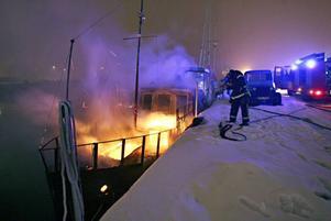 Båten var övertänd när Räddningstjänsten kom till Södra Skeppsbron. Polisen misstänker att branden var anlagd.