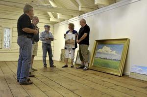 Tavlor. Planeringsgruppen har tre dagar på sig att få upp alla tavlor och fotografier på väggarna. Foto: Linda Wall