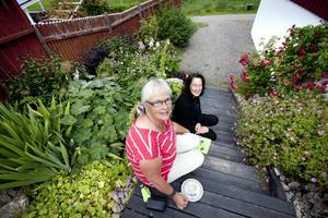 Birgitta och Marie Eriksson njuter av de färggranna rabatterna som pryder entrétrappen upp till Anna-Karin Tillströms trädgård Landet Krokus.