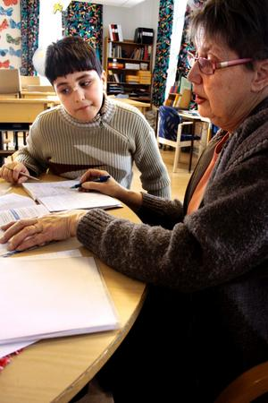 Tystnaden sänker sig i klassrummet då de flesta eleverna gått hem. Men några stannar kvar.  Margareta Käck hjälper Abdullah Dhafer med matteläxan.