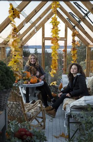Karin, hunder Okra och dottern Linn myser i det Allhelgonapyntade växthuset.