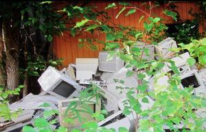 Högar med gammal elektronik ligger kastade i det fria.