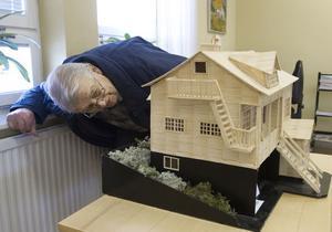 Skaparen själv, Olle Lundgren, kikar in i den modell som visar grannens hus hemma i byn Skålsvedja.