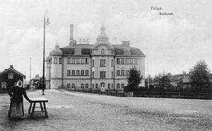 Det nybyggda badhuset från Fisktorget. Vykortet såldes i badhusets kassa. Torghandlerskan är Fläsk-Mina (Mina Bergström). Timmerhuset bakom är hennes bostad. Ljusreklamskylten med