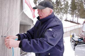 Funktionären Birger Persson sätter upp reklambanderoller inför helgens SM-fest i Åsarna.