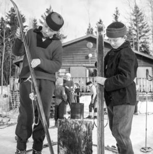 Det gäller att sköta utrustningen. Här är två gossar som förbereder en tur på skidor.
