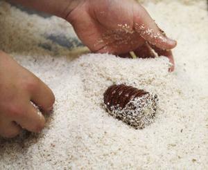 Här blir det en färdig kokosboll. En stor del av tillverkningen sker för hand i fabriken.