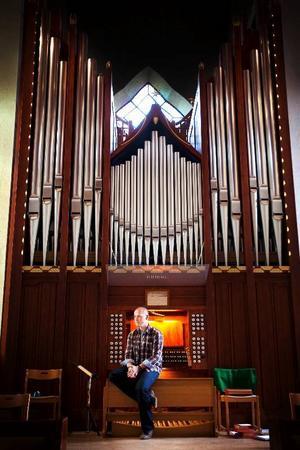 Östersunds vackraste arbetsrum? Nicklas Strandberg tillsammans med en av sina bästa kompisar, Stora kyrkans orgel.Foto: Håkan Luthman