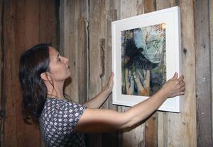 Victoria Engholm hänger upp sin tavla i blandteknik,