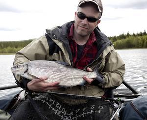 Börje Mattsson med en sik på 2,6 kilo som han fångade i Ljusnan, Härjedalen, från sin pontonbåt.