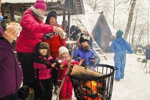 Sigrid Knardal Persson med dottern Line samt Therese Ahlström och hennes döttrar Tilde och Ellen värmer händerna vid elden.