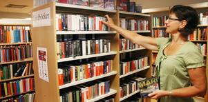 Karin Skogens, bibliotekarie, framför den populära hyllan med ljudböcker.