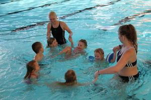 Maggie Wiksten och Felicia Engblom leder barnen, ett steg i sänder, mot simkunskap.