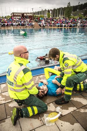 Den årliga livräddaruppvisningen för årskurs 2 och årskurs 3, på Lugnets friluftsbad. Ambulanspersonalen utför första hjälpen på en nödställd.