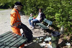 Nära lekplatsen. Maj-Britt plockar skräp. Mats Lindholm och hans Teodor försöker att koppla av.